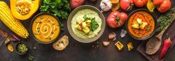 Autumn soups. Set of various seasonal vegetable soups and organic ingredients on dark background, top view, banner. Homemade colourful seasonal vegan soups.