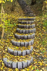 Autumn stair path, scene with stone steps stairs in autumn forest. The stair path in Autumn. Beautiful path up strewn with autumn yellow leaves. Zen, growth concept.