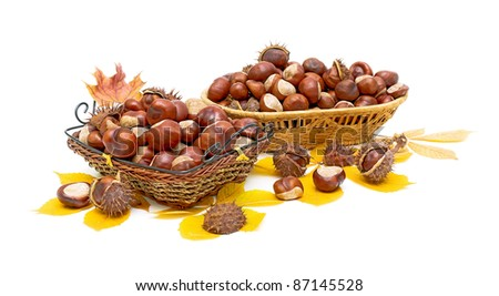 Autumn Still Life - mature chestnuts in a wicker basket on a white background.