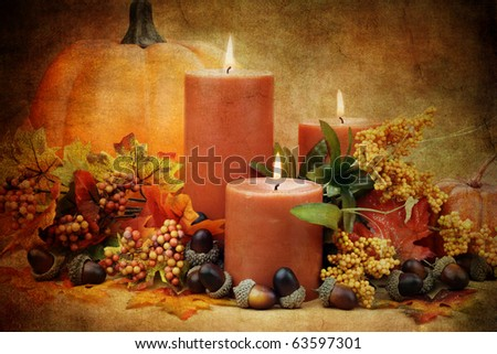 Autumn still life of burning candles surrounded by colorful leaves, pumpkins and acorns.