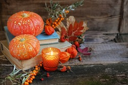 autumn still life. pumpkins, autumn leaves and books on wooden background. fall season, thanksgiving holiday, Halloween concept