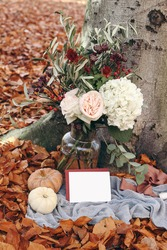 Autumn still life scene. Garden party celebration, picnic with pumkins. Rose flowers bouquet with olive branches. Red beech leaves ground. Blank greeting card mock up scene. Thanksgiving, Halloween.