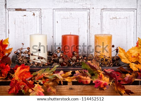Autumn still life with candles and leaves with an antique wood panel for background