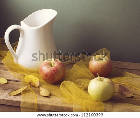 Autumn still life with leaves and apples. Arrangement on wooden table.