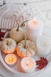 Autumn still life with white pumpkins and burning candles close-up. Cozy fall composition