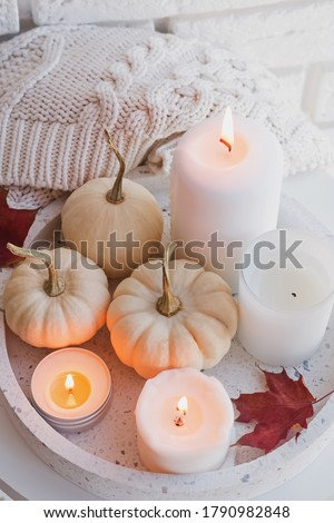 Autumn still life with white pumpkins and burning candles close-up. Cozy fall composition Foto stock ©