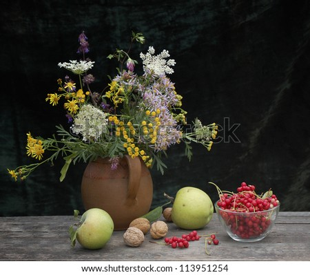autumn still life with wild flowers, apples, nuts and berries