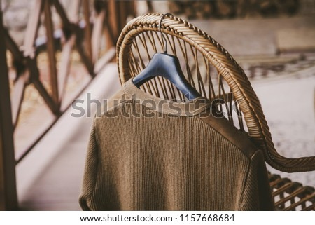 Autumn story. A woolen knitted jacket hangs on a hanger on the back of a wicker chair on the veranda #1157668684