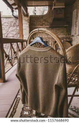 Autumn story. A woolen knitted jacket hangs on a hanger on the back of a wicker chair on the veranda #1157668690