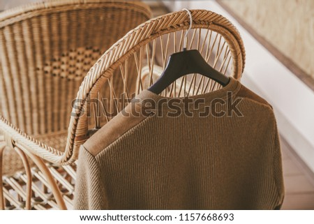 Autumn story. A woolen knitted jacket hangs on a hanger on the back of a wicker chair on the veranda #1157668693