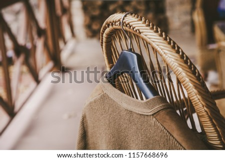 Autumn story. A woolen knitted jacket hangs on a hanger on the back of a wicker chair on the veranda #1157668696