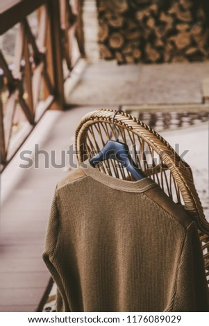 Autumn story. A woolen knitted jacket hangs on a hanger on the back of a wicker chair on the veranda #1176089029