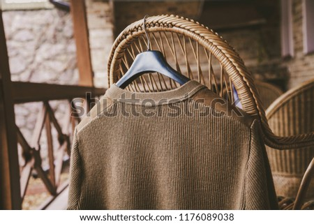 Autumn story. A woolen knitted jacket hangs on a hanger on the back of a wicker chair on the veranda #1176089038
