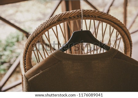 Autumn story. A woolen knitted jacket hangs on a hanger on the back of a wicker chair on the veranda #1176089041