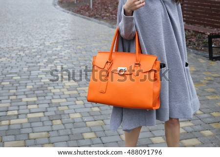 Autumn street fashion look. Young brunette girl in a gray knitted long dress with large bright orange leather bag in hand in the park.