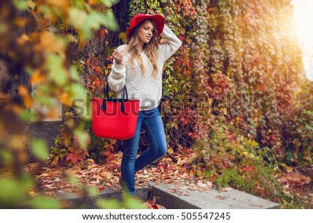 Autumn street fashion look. Young girl in nice clothes posing with large bright bag in hand in the park.