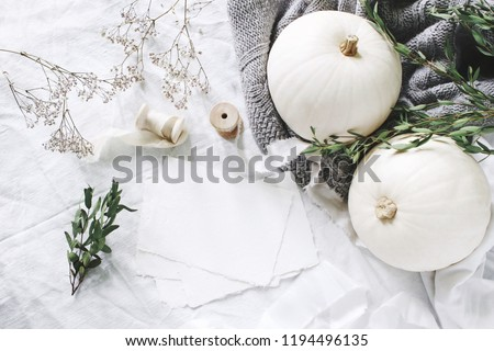 Autumn styled photo. Feminine wedding desktop stationery mockup scene with blank greeting card, eucalyptus, ribbons, white pumpkins and gypsophila flowers. Table background. Thanksgiving. Flat lay.