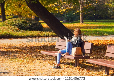 Autumn sunny day afternoon in the park, young lady is reading a book, girl is sitting on park bench with shopping bag, autumn colourful leaves covering sidewalk and grass, relax in city park