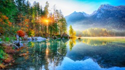 autumn sunrise of Hintersee lake. Beautiful scene of trees near turquoise water of Hintersee lake. Location: resort Ramsau, National park Berchtesgadener Land, Upper Bavaria, Germany Alps, Europe