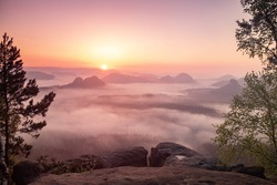 Autumn sunrise, Saxon Switzerland. Fantastic colorful sunrise on the top of the rocky mountain with the view into misty valley