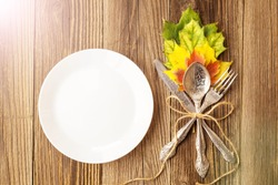 Autumn Table setting. Thanksgiving dinner plate with fork, knife and leaves on rustic wooden table background. Top view, copy space, place for text, toned