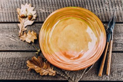 Autumn Table setting. Thanksgiving dinner plate with fork, knife and leaves on rustic wooden table background. Top view, copy space, place for text.