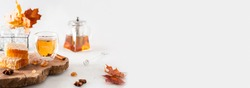Autumn tea banner. Autumn hot tea with spices in glass cup, teapot, honey combs and falling leaves on a white background. Copy space for text, product place. Cozy fall, hygge