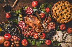 Autumn Thanksgiving, Friendsgiving, family gathering dinner. Flat-lay of Fall table with roasted duck in seasonal fruits, apple pie and red wine decorated with leaves over rusty background