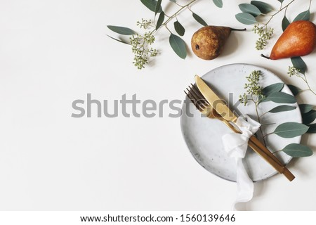 Autumn thanksgiving table place setting. Golden cutlery, porcelain plate, berry eucalyptus leaves and branches, silk ribbon and pear fruit on white table background. Fall wedding. Flat lay, top view. Сток-фото ©
