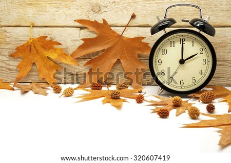 Autumn Time Change / Fall Back / Maple Leaves and an Alarm Clock on a Wooden Background