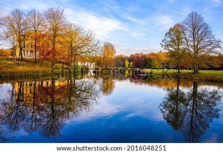 Autumn trees are reflected in the water of the lake. Autumn lake view. Lake in autumn park. Autumn lake landscape