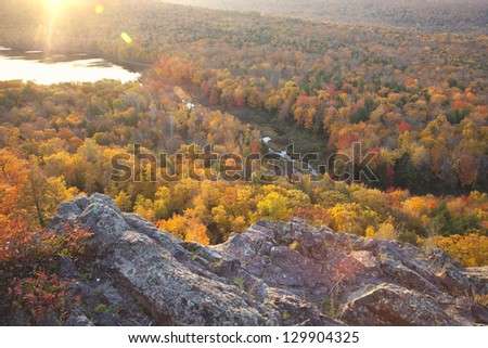 Autumn trees in full color with rocky cliff edge at Lake of the Clouds Michigan. Taken at sunrise.