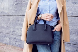 Autumn trendy outfit woman in stylish beige coat and jeans with black big bag