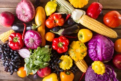 Autumn vegetables and fruits on a wooden background.