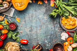 Autumn vegetables cooking preparation . Pumpkin, tomatoes, root vegetables and mushrooms ingredients on dark rustic background for  Thanksgiving Day recipes or menu card, top view, frame