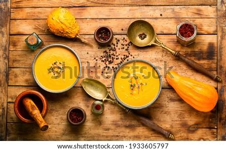 Autumn vegetarian pumpkin cream soup.Pumpkin soup on wooden rustic table