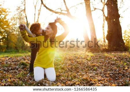 Autumn vibes, family portrait. Charming mom and her red hair daughter have fun sitting on the fallen leaves in the park full of evening sun #1266586435