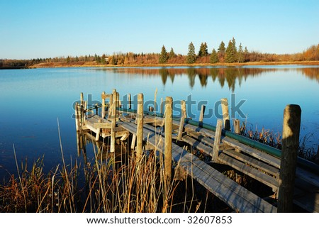 Autumn view of the serene astotin lake, blue sky and shore reflections in elk island national park, edmonton, alberta, canada
