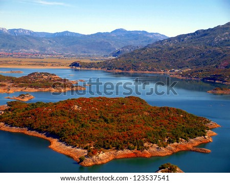 Autumn view of the undulating coastline with islands and colorful shrubs Slansko famous Lake near Niksic in Montenegro
