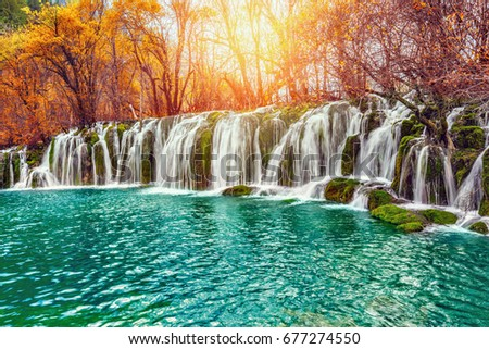 Autumn view of the waterfall with pure water at sunrise time. Jiuzhaigou nature reserve, Jiuzhai Valley National Park, China.
