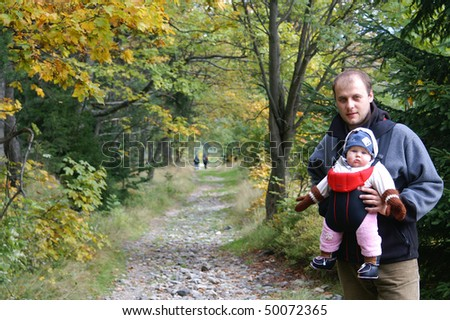 Autumn walk in the mountains with a child in a baby sling