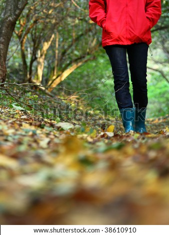 Autumn walk with copy space. Woman walking in the forest on a beautiful fall day.