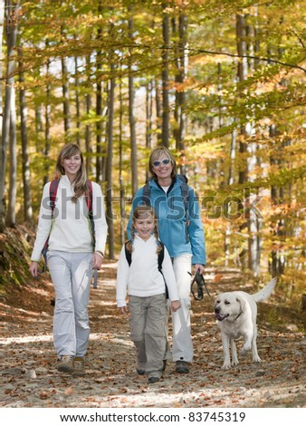 Autumn walking in forest - family with dog on trek (copy space)