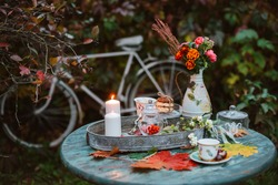 autumn warm evening in the backyard, cozy patio. Autumn leaves lie on a wooden antique round table with crockery cups and cookies burning candle. autumn backyard dark.