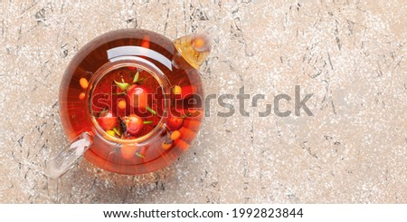 Autumn warming tea with sea buckthorn and rosehips in a glass teapot on the table. Top view.