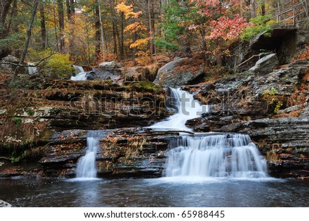 Autumn Waterfall in mountain with foliage and woods over rocks. Factory Falls from Dingmans Falls.
