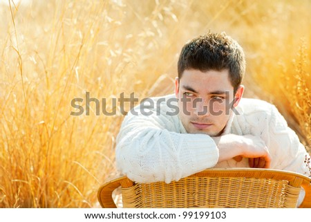 Autumn winter man portrait  in golden grass field with turtleneck sweater - stock photo