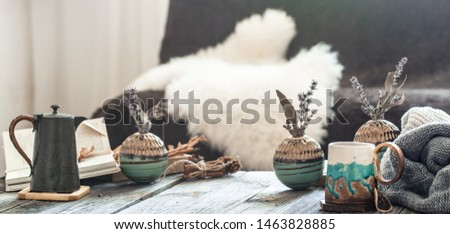 Autumn - winter still Life in a homely atmosphere with decorative items in the living room . With a hot drink on a wooden table.