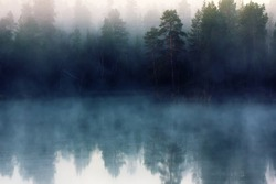 Autumn with mirrored pine forest and misty Northern river. Fog rises above the water at dawn, nascent day and nascent freedom of travel. Lapland, Scandinavia
