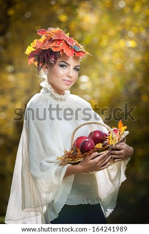 Autumn Woman. Beautiful creative makeup and hair style in outdoor shoot .Beauty Fashion Model Girl with Autumnal Make up and Hair style. Fall. Beautiful fashionable girl holding a basket with apples .